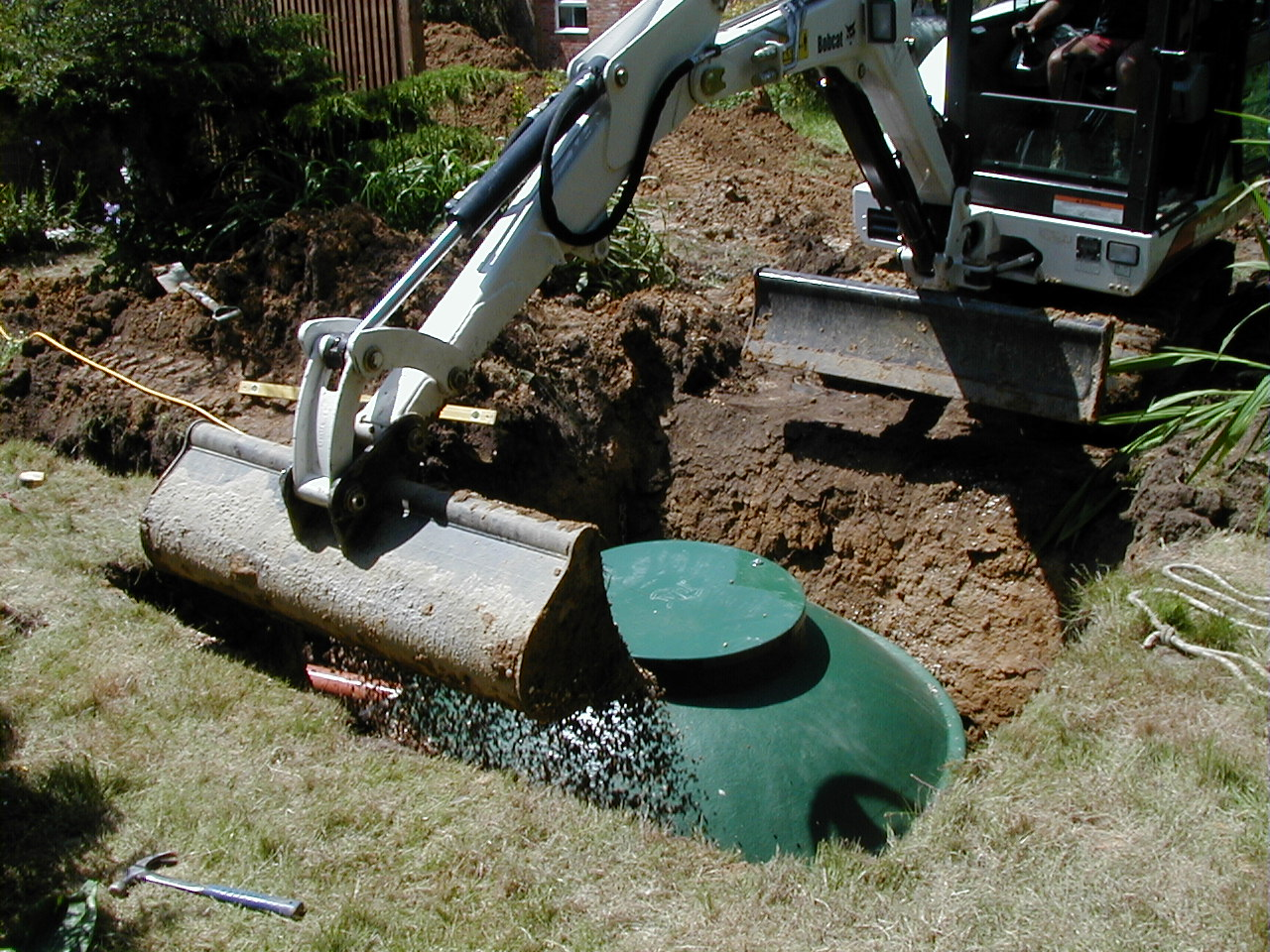 A digger covering dirt over a diamond sewage treatment plant during installation